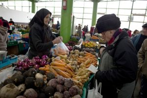 A man purchases vegetables at a market in Bucharest, Romania, on Thursday, Jan. 14, 2010. Romania's credit rating outlook may be raised as Parliament prepares to pass the 2010 budget this week in a move that would unfreeze a $30 billion bailout loan. Photographer: Davin Ellicson/Bloomberg